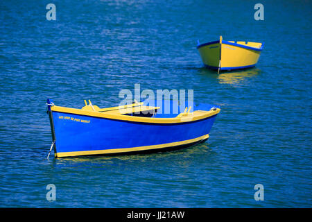Two bright blue and yellow rowing boats on a calm deep blue sea. - Stock Photo