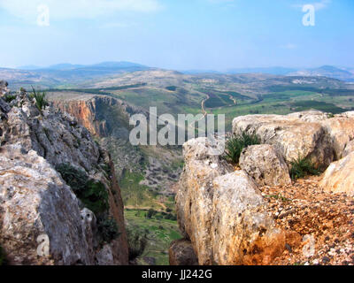 A cleft between two rocky mountains shows a path to distant towns from Mount Arbel next to the Sea of Galilee in - Stock Photo
