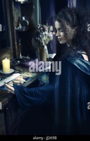 Portrait of a Beautiful mysterious woman fortune teller reading Taror cards at a table, Tarot card reader, devination - Stock Photo