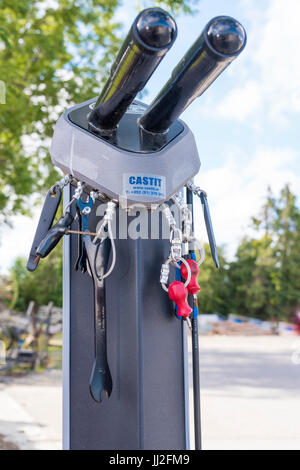 Tools attached by steel cables for repairing bicycles on a bike rack at a roadside filling station in Ireland.
