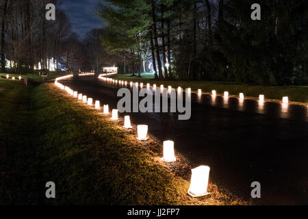 Burke, United States - December 24, 2016: Christmas Eve candle lights in paper bags at night along road illuminated - Stock Photo