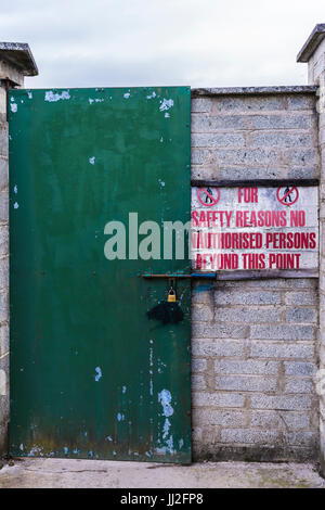 Sign at the locked steel door at an industrial site 'for safety reasons no unauthorised persons beyond this point'. - Stock Photo