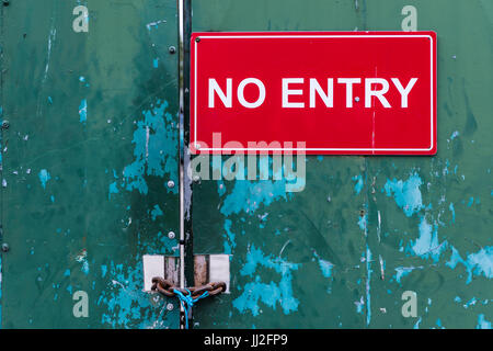 Locked steel door at an industrial site saying 'No Entry' - Stock Photo