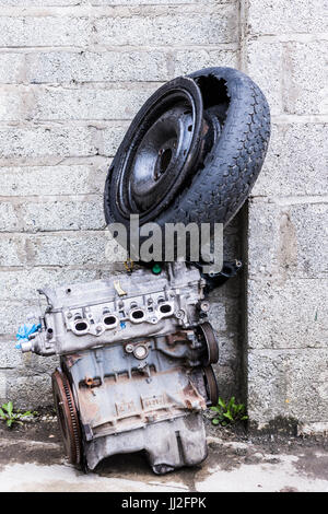 Old engine and car wheel with tyre dumped against an old breeze block wall. - Stock Photo