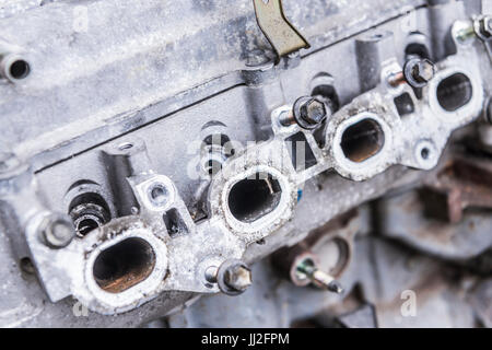 Exhaust gas exit ports on an old engine block with the exhaust manifold removed. - Stock Photo