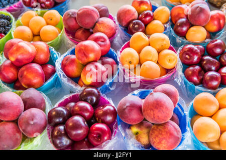 Closeup of many summer fruit in baskets in farmers market on display, including peaches, plums, nectarines and apricots - Stock Photo