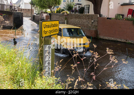Sign saying 'unsuitable for cyclists' at the ford across the river Sid at Sidmouth, Devon, with a van crossing the - Stock Photo