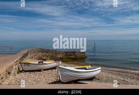 Fishing boats pulled up onto the shale pebble beach at Sidmouth,Devon, at the Port Royal area of the seafront. - Stock Photo