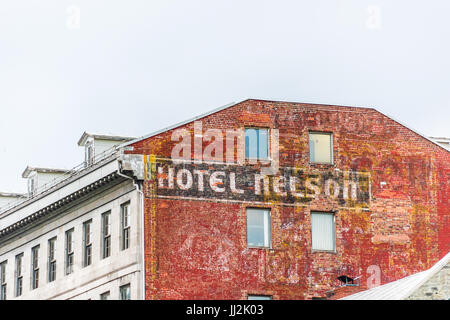 Montreal, Canada - May 27, 2017: Old town area with closeup of Hotel Nelson sign on brick wall in Quebec region - Stock Photo