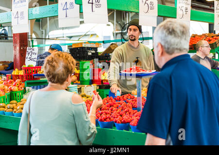 Montreal, Canada - May 27, 2017: Man selling produce by fruit stand with woman buying strawberries at Jean-Talon - Stock Photo
