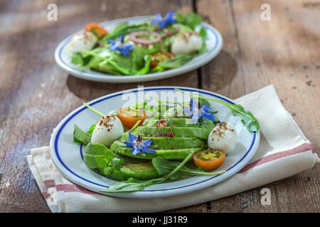 plates of sliced avocado on toast bread with spices and mozzarellaon dishcloth with borage decoration on wooden - Stock Photo