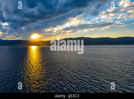 The sun's rays shine on a lone boat at sunset along the Sicilian Coast of Italy - Stock Photo