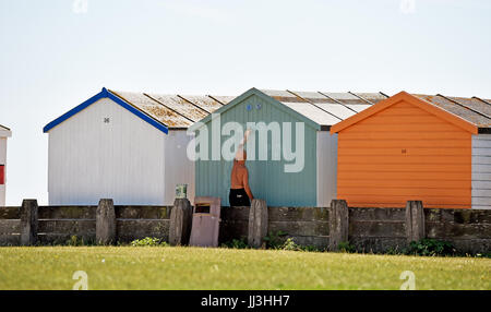 Lancing Sussex, UK. 18th July, 2017. Time to paint the beach hut on a beautiful hot sunny day at Lancing beach near - Stock Photo