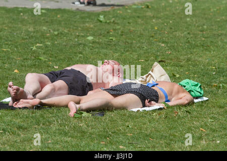 London, UK. 18th Jul, 2017. A couple sunbathe in Victoria Gardens as London experienced sunshine and warm weather - Stock Photo