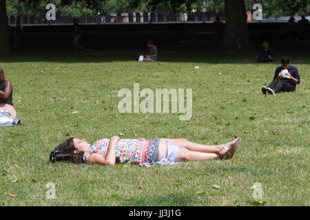 London, UK. 18th Jul, 2017. A woman sunbathes in Victoria Gardens as London experienced sunshine and warm weather - Stock Photo