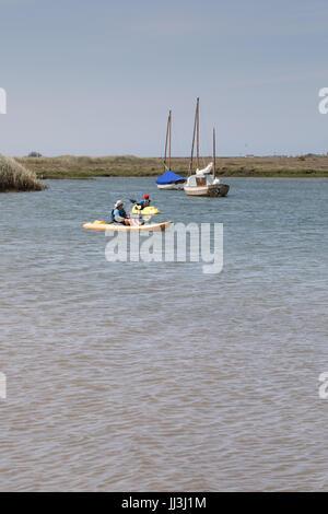Brancaster, Norfolk, UK. 18th July, 2017. UK Weather: Hot sunny spells on Norfolk coast. Children take kayaking lessons in warm weather in harbour Credit: WansfordPhoto/Alamy Live News