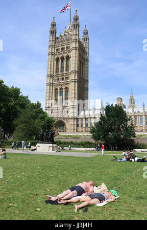 London, UK. 18th July, 2017. A couple sunbathe in Victoria Gardens as London experienced hot weather on a sunny - Stock Photo