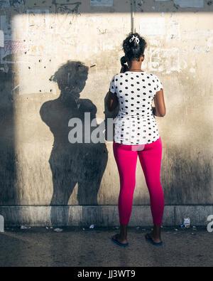 Woman uses a public pay phone in Havana, Cuba - Stock Photo