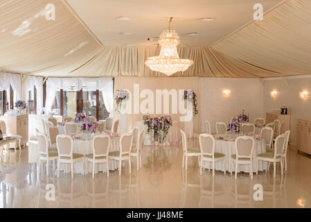 Interior of a wedding decorated restaurant in cream colors - Stock Photo
