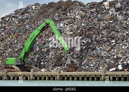 Scrap metal pile waiting for recycling with crane, Newhaven port, East Sussex - Stock Photo
