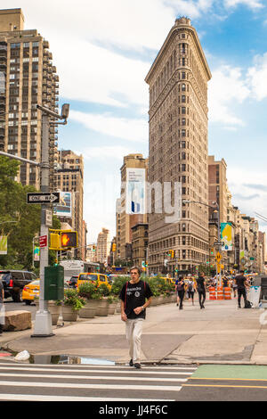 NEW YORK CITY - JULY 15, 2017: New York City street scene with historic Flatiron Building and pedestrians seen from - Stock Photo