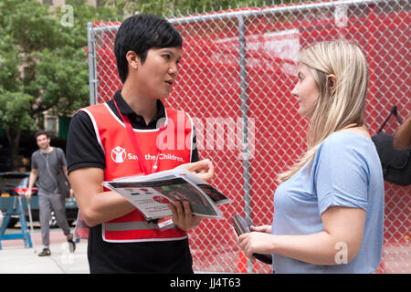 A canvasser for 'Save The Children' organization talks to a woman about recurring contributions (donations) and - Stock Photo