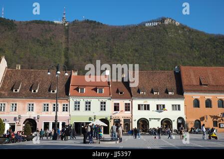 View of Council Square (Piata Sfatului) with Brasov sign in the mountain, Brasov, Romania - Stock Photo