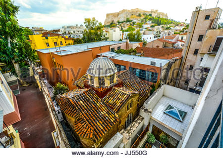 Window view of an ancient Church in Athens Greece squeezed in among the town buildings with the Acropolis and Parthenon - Stock Photo