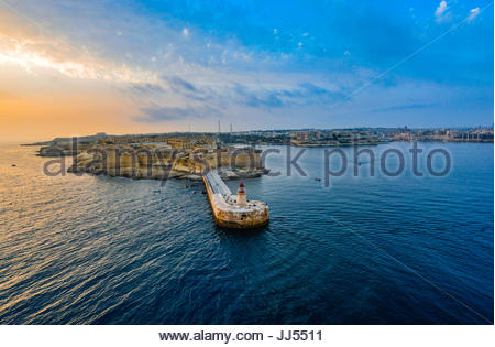 Sunrise view of the Ricasoli Point lighthouse at the Valletta port on the Mediterranean island of Malta on a warm - Stock Photo
