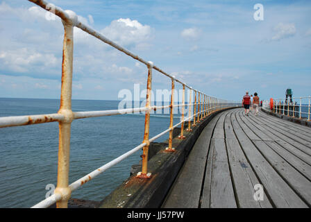 People walking along Whitby west pier, North Yorkshire Great Britain seaside town. Taken July 2017 - Stock Photo