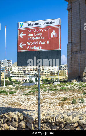 Typical Maltese street name sign and information sign showing the way to some popular destinations - Mellieha, Malta. - Stock Photo