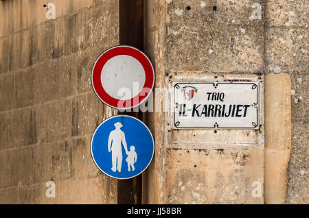 Typical Maltese street name sign and two traffic signs - Rabat, Malta. - Stock Photo