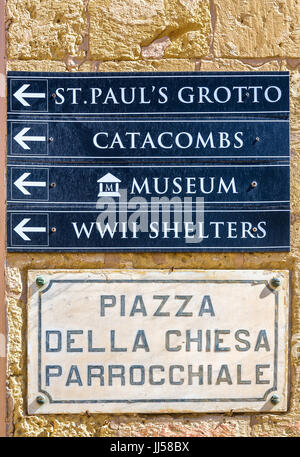 Marble street name sign and information signs showing the way to some popular destinations - Rabat, Malta. - Stock Photo