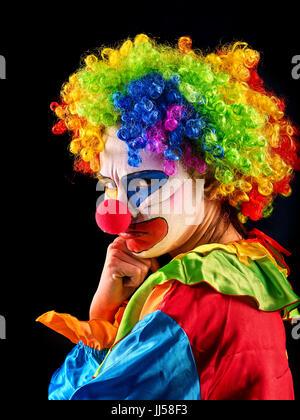 Evil clown on black background. Portrait of crazy woman. - Stock Photo