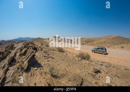 Car on gravel road in the Namib desert, Namib Naukluft National Park, main travel destination in Namibia, Africa. - Stock Photo