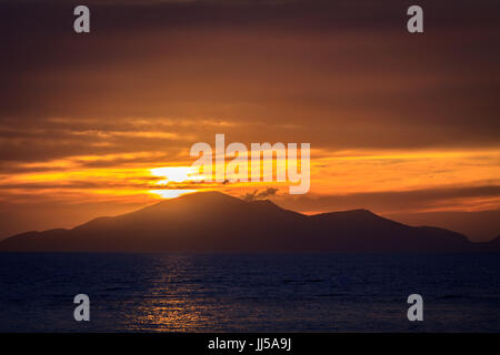 Wonderful sunset behind mountains peak protruding from ocean. - Stock Photo