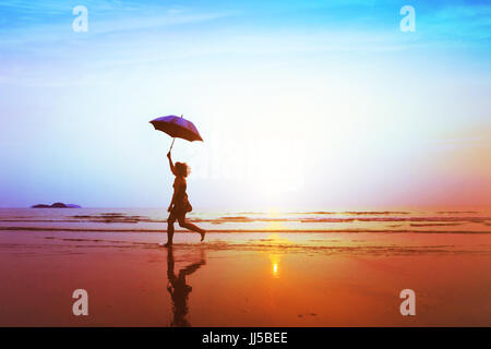 silhouette of happy carefree girl with umbrella jumping on the beach at sunset, freedom and joy concept - Stock Photo