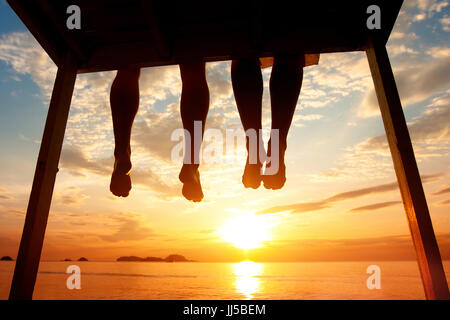 happiness concept, silhouette of feet of couple sitting on the pier at sunset beach - Stock Photo