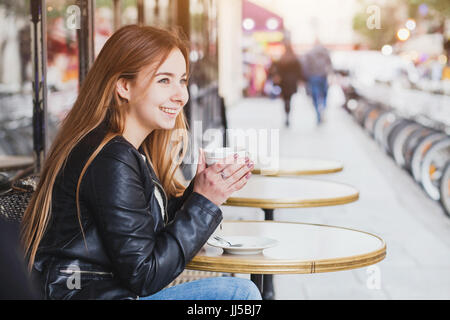 happy smiling attractive young woman with cup of coffee in street cafe in Europe, pretty girl in Paris - Stock Photo