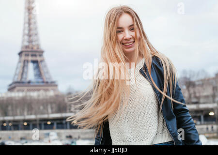 happy young woman in Paris near Eiffel tower, smiling girl traveling portrait, student in Europe - Stock Photo