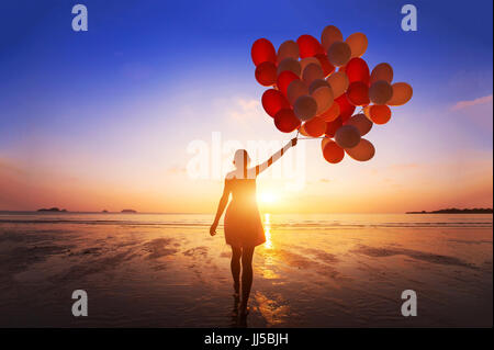 inspiration, joy and happiness concept, silhouette of woman with many flying balloons on the beach - Stock Photo