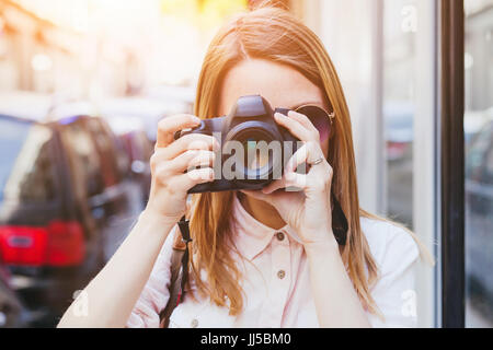 photographer taking photo with dslr professional camera on the street, portrait of woman tourist - Stock Photo