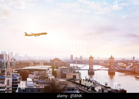 travel to London by flight, airplane in the sky over Tower Bridge - Stock Photo