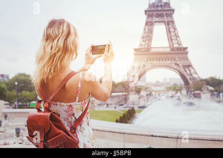 tourist in Paris visiting landmark Eiffel tower, sightseeing in France, woman taking photo on mobile phone - Stock Photo