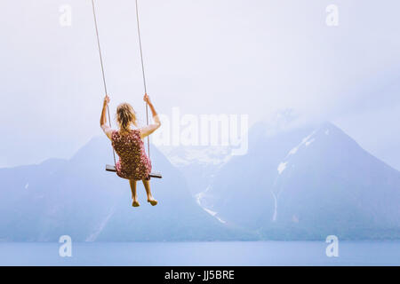 happiness concept, happy girl child on the swing on beautiful mountain landscape background - Stock Photo