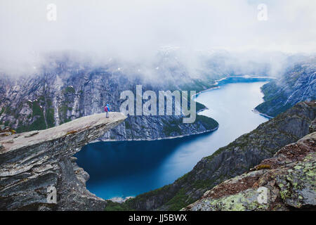 Trolltunga hike in Norway in cloudy bad weather, hiker tourist backpacker standing on the cliff and looking at fjord - Stock Photo