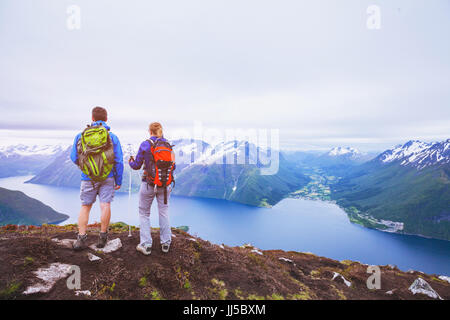 couple of hikers on top of the mountain, group of backpackers traveling in Norway fjords, people looking at beautiful panoramic landscape Stock Photo