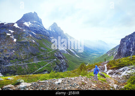 Trollstigen in Norway, tourist looking at mountain road in stunning beautiful landscape - Stock Photo