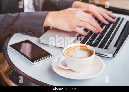 working on computer online, woman checking email on laptop in cafe, social network or internet concept - Stock Photo
