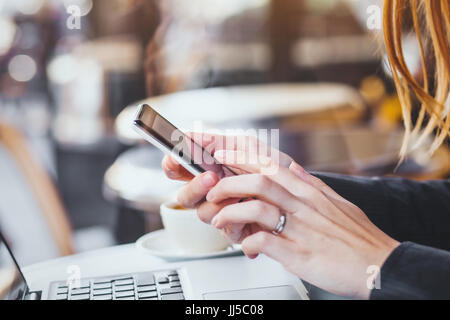 woman hands holding smartphone on city background - Stock Photo